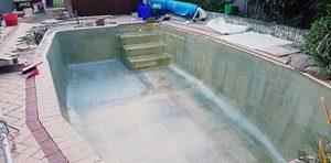 applying-matte-layer-of-fibreglass-to-concrete-pool-resurfacing